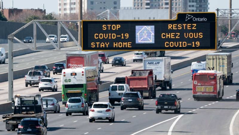 Traffic on Highway 401 in Toronto passes under a COVID-19 sign on Monday April 6, 2020. THE CANADIAN PRESS/Frank Gunn