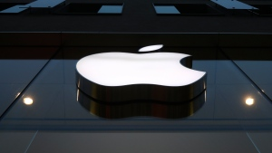 The logo of Apple is illuminated at a store in the city center in Munich, Germany, Wednesday, Dec. 16, 2020. (AP Photo/Matthias Schrader)