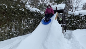 Barb Wiens sliding down a luge built in her backyard as part of the Winterlude re-creation. Ottawa, On., Feb. 19, 2020. (Tyler Fleming / CTV News Ottawa)