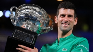 Serbia's Novak Djokovic holds the Norman Brookes Challenge Cup after defeating Russia's Daniil Medvedev in the men's singles final at the Australian Open tennis championship in Melbourne, Australia, Sunday, Feb. 21, 2021.(AP Photo/Andy Brownbill)