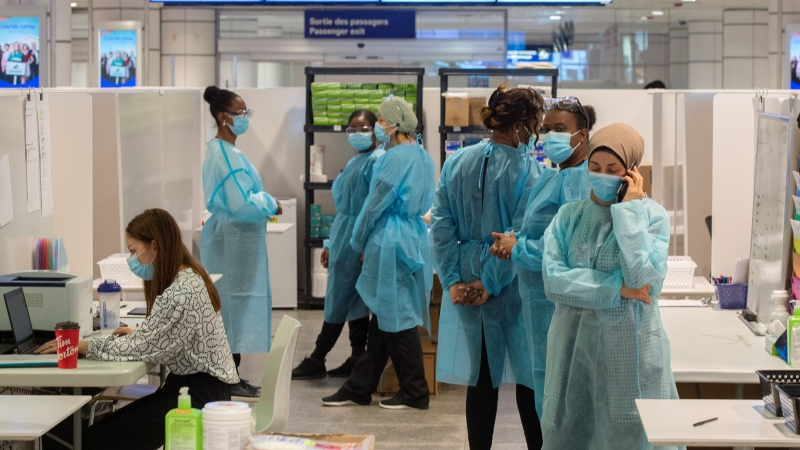 Healthcare workers wait for airline passengers at a COVID-19 testing center at Trudeau Airport in Montreal, Friday, Feb. 19, 2021. The federal government announced which hotels will be used for all travelers entering Canada by air to quarantine for three days at their own expense. THE CANADIAN PRESS/Ryan Remiorz