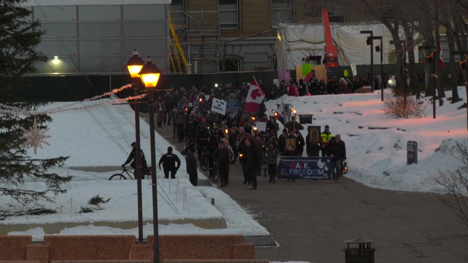 The Calgary-based Walk for Freedom group marched to the Alberta legislature on Feb. 20, 2021, carrying burning torches and signs protesting COVID-19 public health measures.
