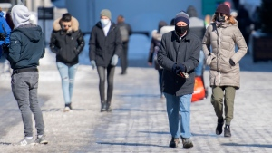 People wear face masks as they walk along a street in Montreal, Sunday, February 21, 2021, as the COVID-19 pandemic continues in Canada and around the world. THE CANADIAN PRESS/Graham Hughes