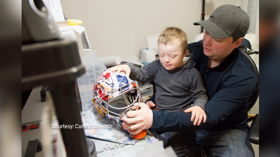 Curtis Schwartz and his son, who has Down syndrome, with the goalie mask commissioned by the Oilers to pay tribute to Joey Moss.