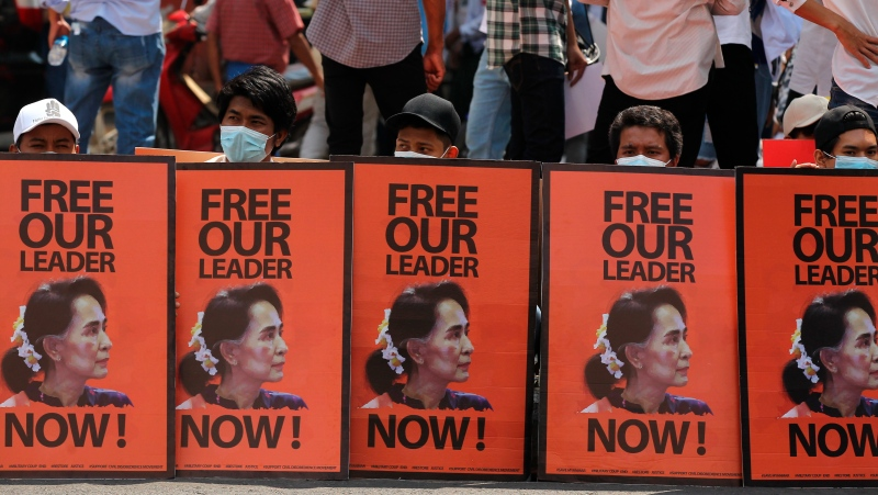Anti-coup protesters sit behind posters with an image of deposed Myanmar leader Aung San Suu Kyi during a rally in Yangon, Myanmar, Monday, Feb. 22, 2021. (AP Photos)
