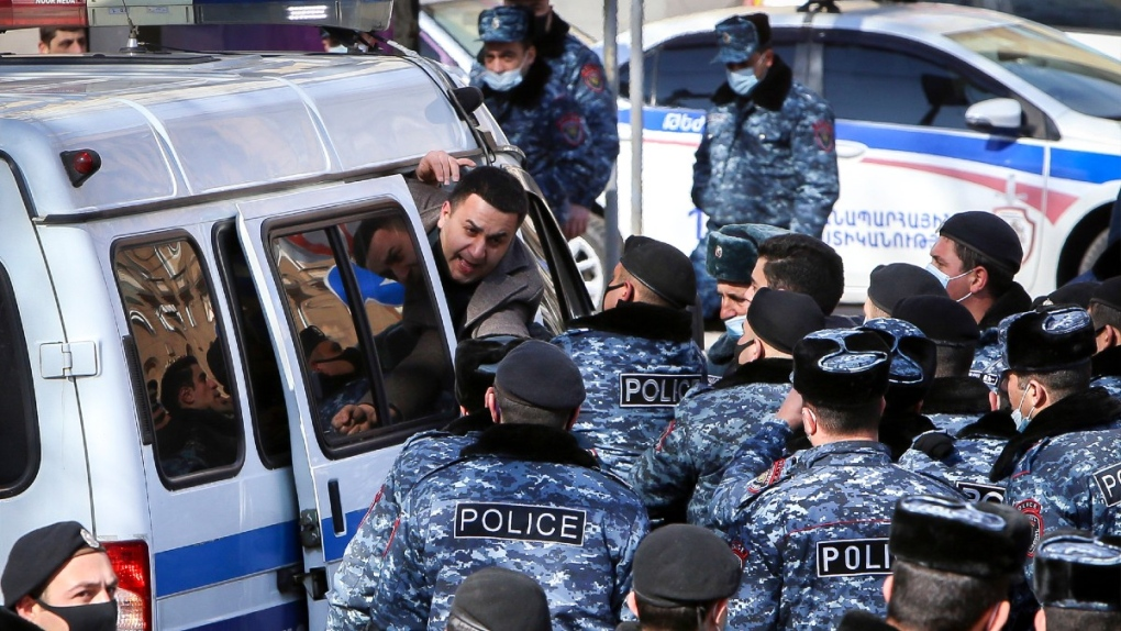 Police detain a protester in Yerevan, Armenia