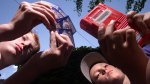 Sam Barr,13, right, checks out his Pokemon trading cards while his friend Sean Stidwell, 12, plays a Pokeman game on a Gameboy in Ottawa, Monday July 12, 1999. (CP PHOTO/Tom Hanson)