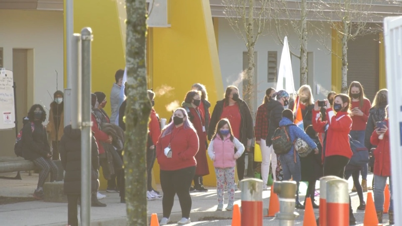 Teachers outside a Surrey school wearing red on Feb. 23, 2020, in support of other schools with confirmed COVID-19 variants.