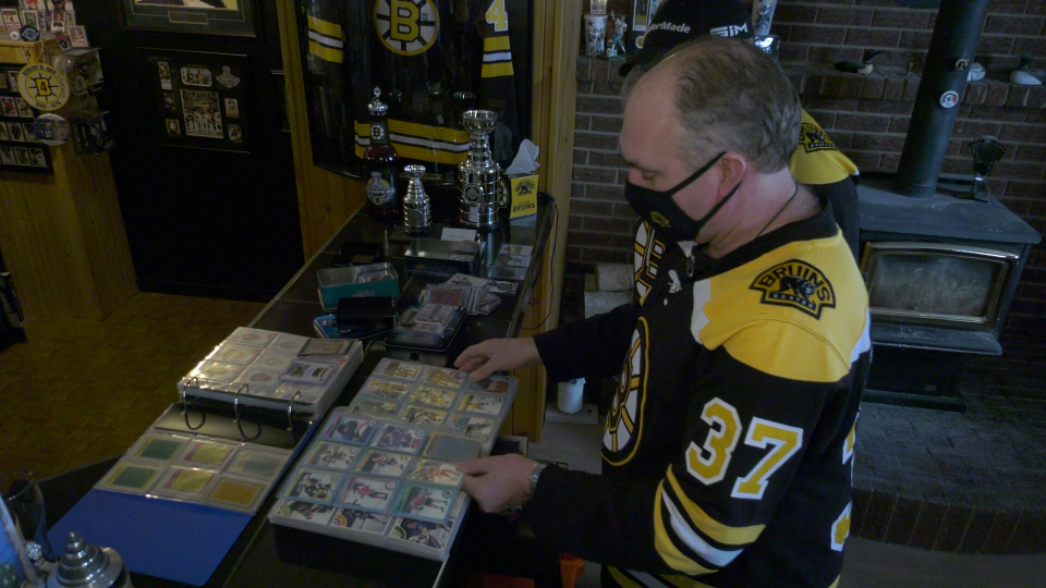 Barry Casselman looks over some old hockey cards from the 1979-80 season. (Nate Vandermeer / CTV News Ottawa)