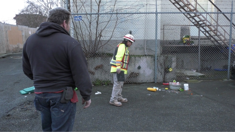 Orb Norrie (who is in the foreground) is seen with a coworker inspecting the 713 needles that were found in the alley this morning: Feb. 23, 2021 (CTV NEws)