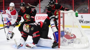 Ottawa Senators right wing Drake Batherson (19) slams Montreal Canadiens left wing Tomas Tatar (90) into the net during first period NHL action in Ottawa on Tuesday, Feb. 23, 2021. THE CANADIAN PRESS/Sean Kilpatrick