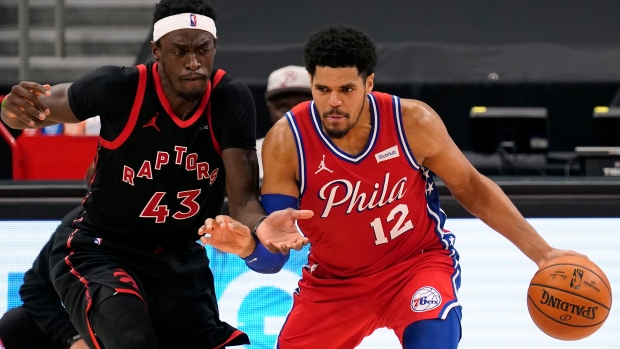 Philadelphia 76ers forward Tobias Harris (12) drives around Toronto Raptors forward Pascal Siakam (43) during the second half of an NBA basketball game Tuesday, Feb. 23, 2021, in Tampa, Fla. (AP Photo/Chris O'Meara)