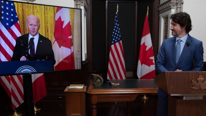 Prime Minister Justin Trudeau looks at United States President Joe Biden as he delivers a statement during a virtual joint statement in Ottawa, Tuesday, February 23, 2021. THE CANADIAN PRESS/Adrian Wyld