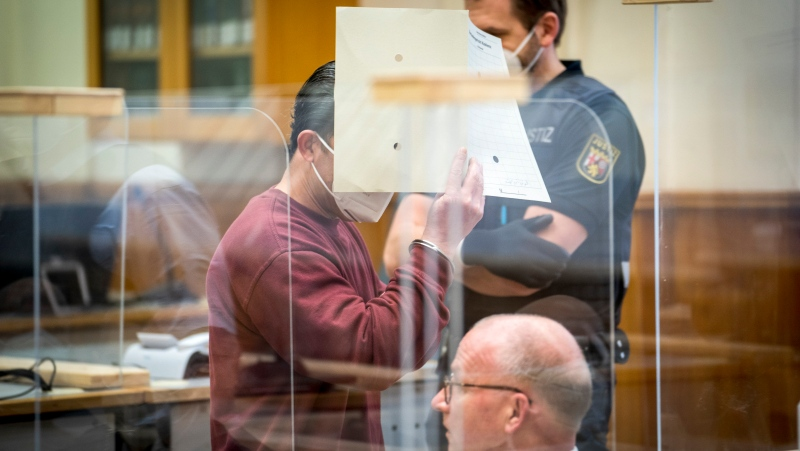 Syrian defendant Eyad Al-Gharib hides his face as he arrives to his hear his verdict in a court room in Koblenz, Germany, Wednesday, Feb. 24, 2021. A German court has convicted the former member of Syrian President Bashar Assad's secret police of facilitating the torture of prisoners in a landmark ruling that human rights campaigners hope will set a precedent for other cases. (Thomas Lohnes/Pool Photo via AP)