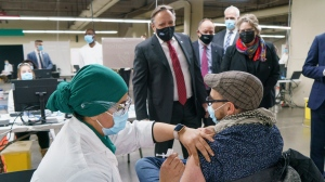 Quebec Premier Francois Legault watches a man get his COVID-19 vaccine at a clinic in Montreal's Olympic Stadium on Tuesday, February 23, 2021. THE CANADIAN PRESS/Paul Chiasson