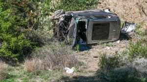 A vehicle rests on its side after a rollover accident involving golfer Tiger Woods along a road in the Rancho Palos Verdes suburb of Los Angeles on Tuesday, Feb. 23, 2021. (AP Photo/Ringo H.W. Chiu)
