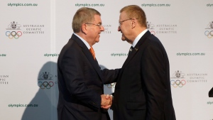 In this Saturday, May 4, 2019 file photo, International Olympic Committee President Thomas Bach, left, shakes hands with Australian Olympic Committee (AOC) President John Coates at the AOC annual general meeting in Sydney, Australia. (AP Photo/Rick Rycroft, File)