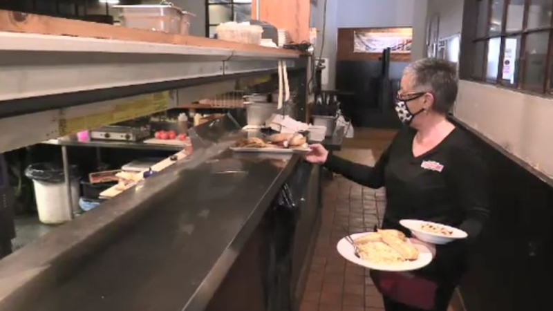 St. Thomas Roadhouse Restaurant server Tracy Tompkins delivers an order Feb 24, 2021. (Brent Lale/CTV London)