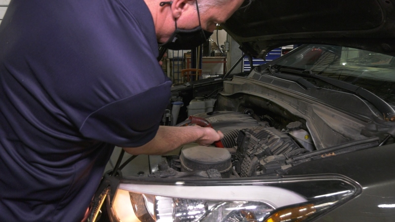 Rich Gregg, owner of Essential Auto Service, clips a battery testing device to a vehicle battery at his Waterloo shop. Tuesday, February 23, 2021. (Ricardo Veneza/CTV Kitchener).