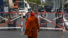 A Buddhist monk walks along a road as police stand watch in Mandalay, Myanmar, Wednesday, Feb. 24, 2021. (AP Photo)