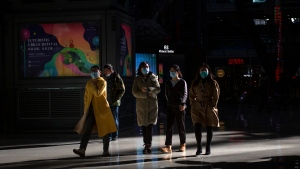 People wearing face masks to protect against the spread of the coronavirus walk through an upscale shopping mall in Beijing, Friday, Jan. 8, 2021. (AP Photo/Mark Schiefelbein)