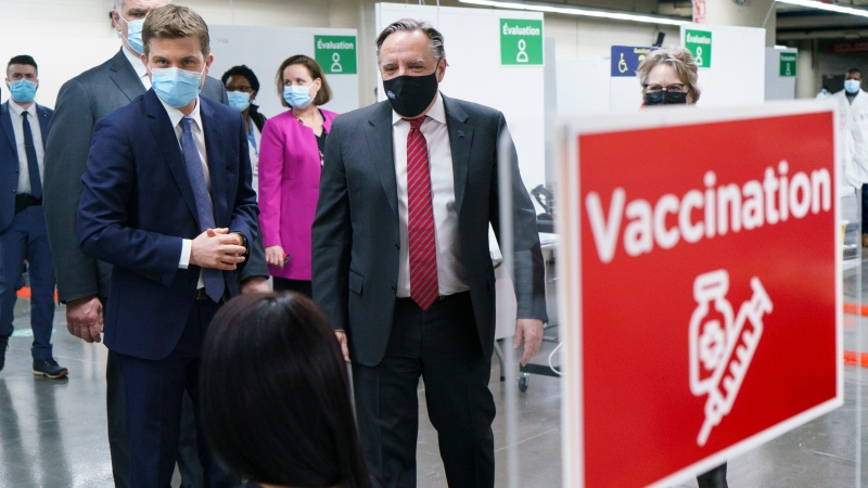 Quebec Premier Francois Legault chats with a woman who just got her COVID-19 vaccine at a clinic in Montreal's Olympic Stadium on Tuesday, February 23, 2021. THE CANADIAN PRESS/Paul Chiasson