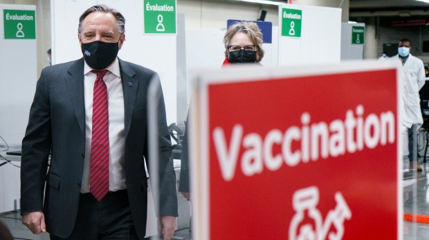 Quebec Premier Francois Legault tours a COVID-19 vaccination clinic in Montreal's Olympic Stadium on Tuesday, February 23, 2021. THE CANADIAN PRESS/Paul Chiasson