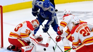 Calgary Flames goaltender David Rittich (33) makes a save on Toronto Maple Leafs left wing Jimmy Vesey (26) as Flames' Christopher Tanev (8) and Joakim Nordstrom (20) defend during first period NHL action in Toronto on Wednesday, February 24, 2021. (THE CANADIAN PRESS/Frank Gunn)