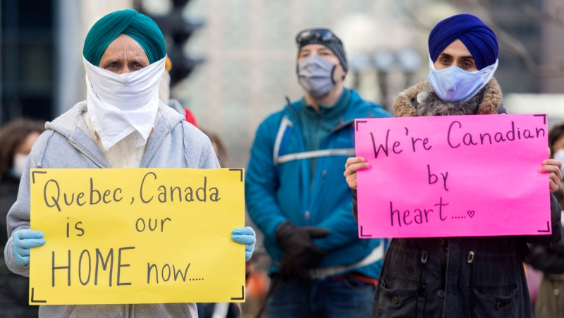People take part in a demonstration outside Quebec Premier Francois Legault's office in Montreal, Saturday, Nov. 21, 2020, where they called on the government to give permanent residency status to all migrant workers and asylum seekers.The COVID-19 pandemic continues in Canada and around the world. THE CANADIAN PRESS/Graham Hughes