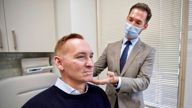 Plastic surgeon Dr. Michael Somenek examines the face of his patient Hudson Young, 52. (AFP)