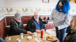 Waitress Tracy Laveque serves patrons as they enjoy dining in at Hunter's Country Kitchen, as Alberta begins Step 1 of a plan to ease restrictions, in Carstairs, Alta., Monday, Feb. 8, 2021. THE CANADIAN PRESS/Jeff McIntosh​