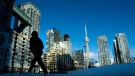 Condo towers dot the Toronto skyline as a pedestrian makes his way through the COVID-19 restricted winter landscape on Thursday January 28, 2021. THE CANADIAN PRESS/Frank Gunn