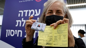 An Israeli medical worker presents her certificate of vaccination after receiving a second Pfizer-BioNTech COVID-19 shot, but the issue of virus passports has divided Europe. (AFP)