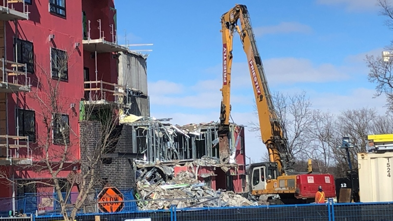 An excavator works at the scene of the building collapse on Teeple Terrace in London, Ont. on Thursday, Feb. 25, 2021. (Jim Knight / CTV News)
