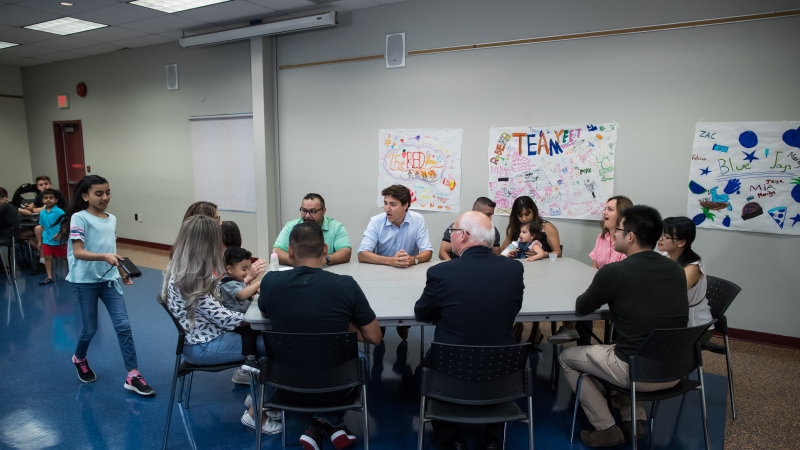 Prime Minister Justin Trudeau, back centre, sits down to speak with families about the Canada Child Benefit during a visit to the Surrey Sport and Leisure Complex, in Surrey, B.C., on Saturday, July 13, 2019. THE CANADIAN PRESS/Darryl Dyck