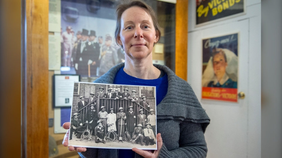Chara Kingston, collections manager at The Army Museum at the Halifax Citadel National Historic Site, displays a photo of an all-Black fire brigade on Thursday, Feb. 25, 2021. The civilian fire wardens were part of the Air-Raid Precautions Group, which was formed by the federal government in 1939 and disbanded in 1945. (THE CANADIAN PRESS/Andrew Vaughan)