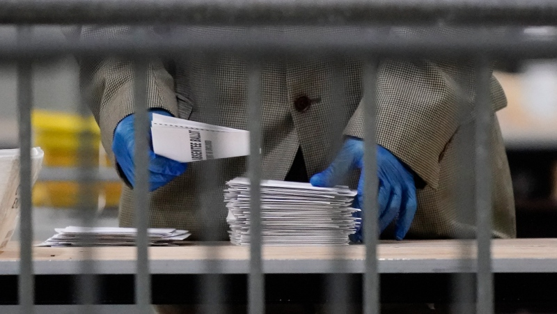 An official counts ballots for Georgia's Senate runoff election at the Georgia World Congress Center on Wednesday, Jan. 6, 2021, in Atlanta. (AP Photo/Brynn Anderson)