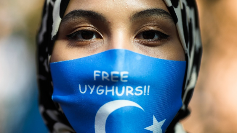 A woman wears a face mask reading 'Free Uyghurs' as she attends a protest during the visit of Chinese Foreign Minister Wang Yi in Berlin, Germany, Tuesday, Sept. 1, 2020. (AP Photo/Markus Schreiber)