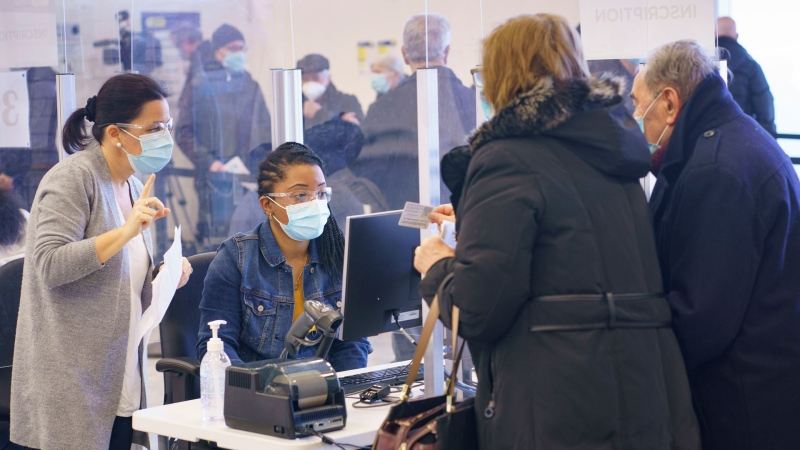 People register to receive their first dose of COVID-19 vaccination in Laval, Que. on Thursday, February 25, 2021, marking the start of mass vaccination in the province of Quebec. THE CANADIAN PRESS/Paul Chiasson