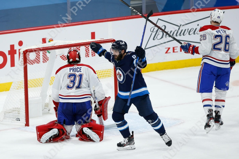 Winnipeg Jets' Mathieu Perreault (85) celebrates Pierre-Luc Dubois' (13) goal against Montreal Canadiens goaltender Carey Price (31) during third period NHL action in Winnipeg on Thursday, February 25, 2021. THE CANADIAN PRESS/John Woods