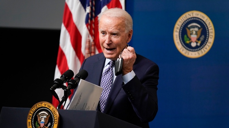U.S. President Joe Biden holds his face mask as he speaks during an event to commemorate the 50 millionth COVID-19 shot, in the South Court Auditorium on the White House campus, Thursday, Feb. 25, 2021, in Washington. (AP Photo/Evan Vucci)