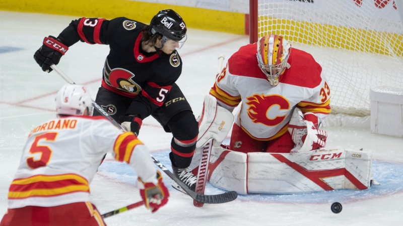 Ottawa Senators' Matthew Peca pressures Calgary Flames goaltender David Rittich as he makes a save during first period NHL action Thursday, February 25, 2021 in Ottawa. THE CANADIAN PRESS/Adrian Wyld