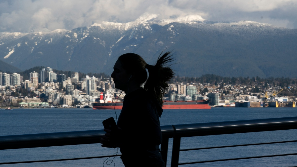 The snow covered North Shore Mountains are seen in the background as a jogger runs along the waterfront in Vancouver, Tuesday, February 9, 2021. THE CANADIAN PRESS/Jonathan Hayward