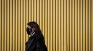 A pedestrian wears a face mask to curb the spread of COVID-19, in Vancouver, on Tuesday, February 16, 2021. THE CANADIAN PRESS/Darryl Dyck