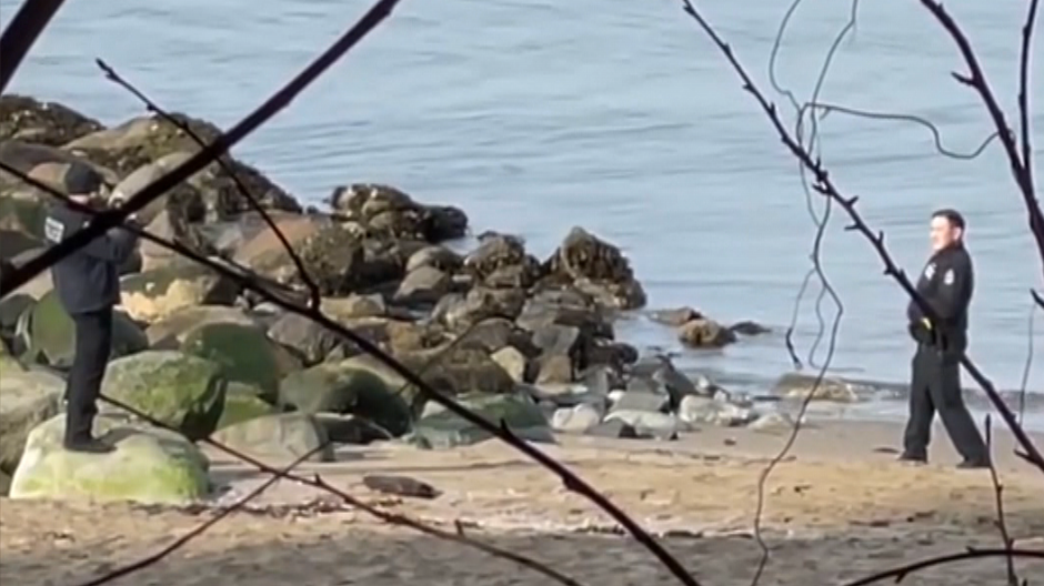 A still image from video shows an officer posing on a Vancouver beach. A body, not pictured, is behind him, the video shows when it pans.