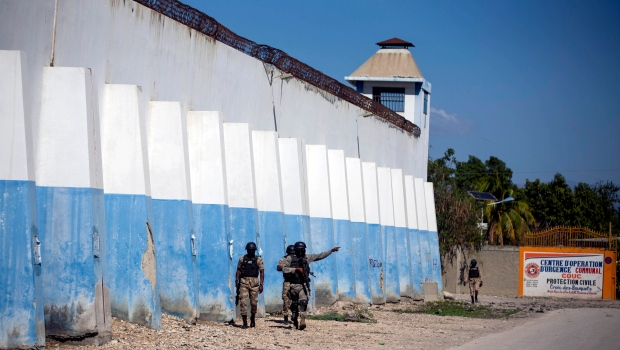 National police officers search for inmates on the perimeters of the Croix-des-Bouquets Civil Prison in Port-au-Prince, Haiti, Thursday, Feb. 25, 2021. (AP Photo/Dieu Nalio Chery)