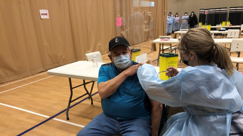 A member of the Beausoleil First Nation receives his first dose of COVID-19 vaccine on Christian Island, Ont. on Fri. Feb. 26, 2021 (Madison Erhardt/CTV News)