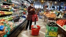 A shopper wears a face mask in the produce section of a grocery store Saturday, April 18, 2020, in the Harlem neighborhood of the Manhattan borough of New York. (AP Photo/John Minchillo)