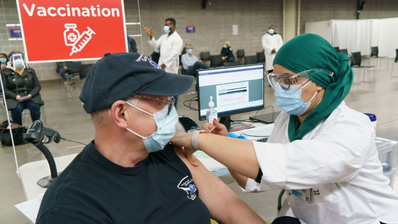 A man receives his COVID-19 vaccine at a vaccination clinic in Montreal's Olympic Stadium on Tuesday, February 23, 2021. THE CANADIAN PRESS/Paul Chiasson