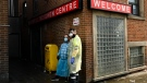 A worker and a paramedic stand outside the Maxwell Meighen Centre helping homeless people as the new COVID-19 variants have spread among homeless populations in a and around the city during the COVID-19 pandemic in Toronto on Wednesday, February 24, 2021. THE CANADIAN PRESS/Nathan Denette